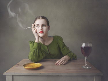 Anna Buczek Young woman sitting at table with cigarette and glass of red wine Women