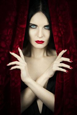 Magdalena Russocka elegant woman behind red curtain