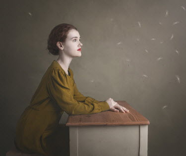 Anna Buczek Young woman watching falling dandelion seeds while sitting at desk Women