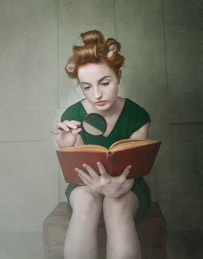 Anna Buczek Young woman with hair rollers reading by magnifying glass Women