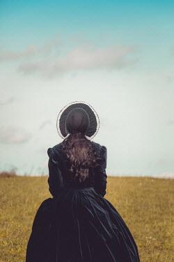 Joanna Czogala Woman with black dress and bonnet in field