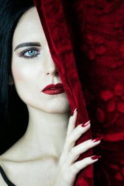 Magdalena Russocka elegant woman peeping behind red curtain