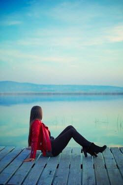 Ildiko Neer Woman in red jacket sitting on jetty Women