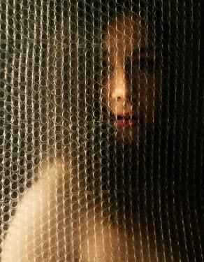 Kirill Sakryukin BRUNETTE WOMAN BEHIND PLASTIC SHEETING Women