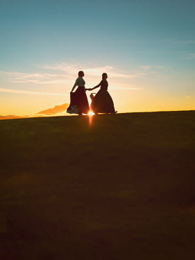 Mary Wethey HISTORICAL WOMAN HOLDING HANDS AT SUNSET ON HILL Women