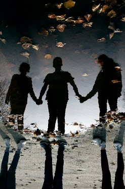 Ute Klaphake Reflection of children holding hands in puddle