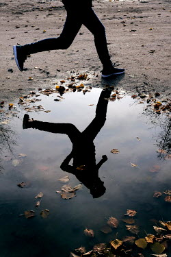 Ute Klaphake Legs of boy running by puddle