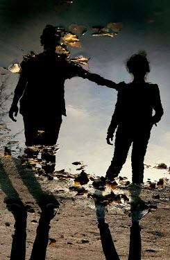 Ute Klaphake Reflection of boy and girl in puddle