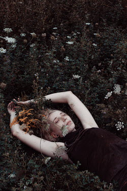 Charlotte Grimm Young woman lying in meadow