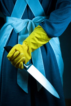Magdalena Russocka close up of woman's hand in rubber glove holding knife