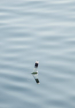 Adrian Leslie Campfield Glass bottle floating in water
