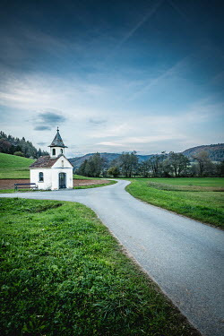 Des Panteva SMALL WHITE CHAPEL BY FORKED ROAD IN COUNTRYSIDE Religious Buildings