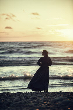 Magdalena Russocka silhouette of historical woman standing on beach at sunset