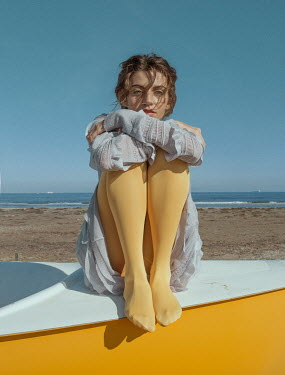 Elisa Paci Young woman in yellow stockings sitting on boat at beach