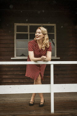 Shelley Richmond Young woman in red polka dot dress leaning on railing