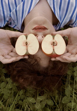 Elisa Paci Young woman holding sliced apple over her eyes