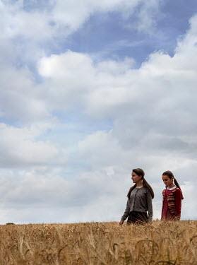 Stephen Mulcahey two teenage evacuees, walking through a  a field of wheat