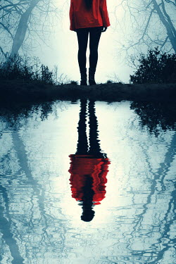 Magdalena Russocka modern woman standing in woods reflected in water