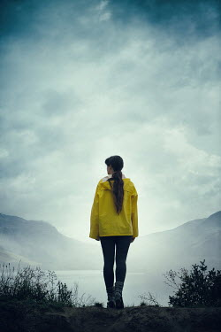 Magdalena Russocka modern woman wearing yellow raincoat standing at lake