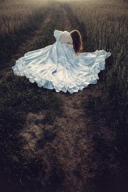 Magdalena Russocka woman in white dress lying down in field