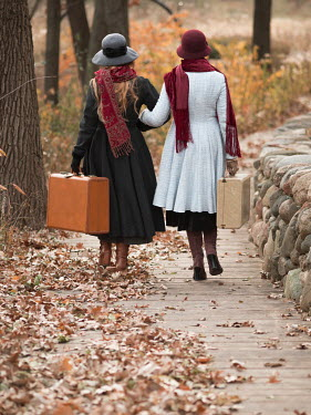 Elisabeth Ansley Young women in vintage hats and coats walking with suitcases on boardwalk
