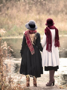 Elisabeth Ansley Young women in vintage hats and coats stand by river