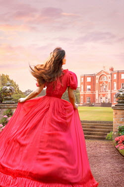 Lee Avison victorian woman in a red evening dress running towards a mansion house
