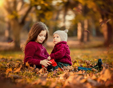 Lilia Alvarado Girl playing in autumn leaves with her baby brother