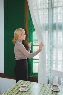 Joanna Czogala Woman looking out kitchen window