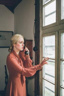 Joanna Czogala Woman talking on telephone by window