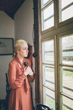 Joanna Czogala Anxious woman holding telephone by window