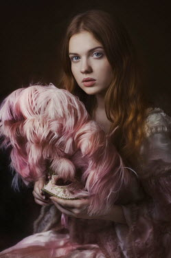 Beata Banach Young woman holding masquerade mask with pink feathers