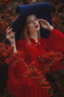 Beata Banach Young woman in red dress and oversized hat