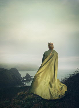 Mark Owen Young woman in green cloak and crown on hill by sea