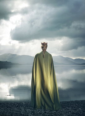 Mark Owen Young woman in green cloak and crown by lake