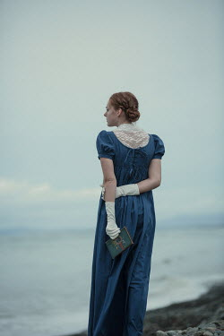 Magdalena Russocka historical woman with book walking on beach