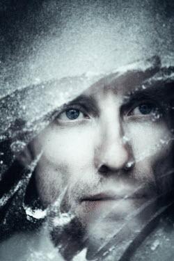 Magdalena Russocka serious man looking through snowy window