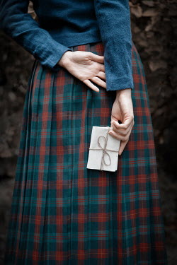 Natasza Fiedotjew Young woman in plaid skirt holding letter Women