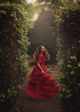 Magdalena Kolakowska Young woman in red dress between hedges
