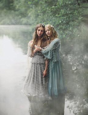 Magdalena Kolakowska Teenage girls wrapped in fishing net standing in river
