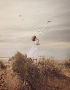 Magdalena Kolakowska Teenage girl whistling with seashell to seagulls on beach