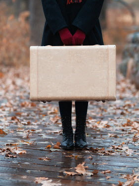 Elisabeth Ansley Teenage girl with vintage coat, suitcase, and boots on boardwalk