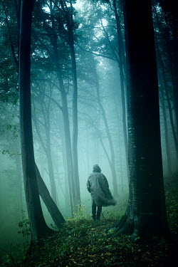 Andrei Cosma Man in hooded coat walking in misty forest