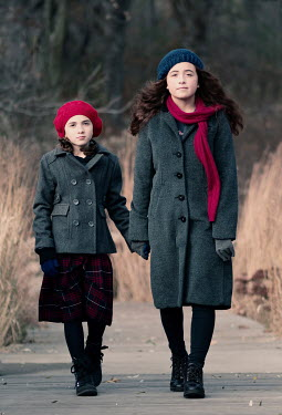 Elisabeth Ansley Sisters in gray coats hold hands while walking on boardwalk