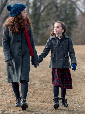 Elisabeth Ansley Sisters in gray coats hold hands while walking in park