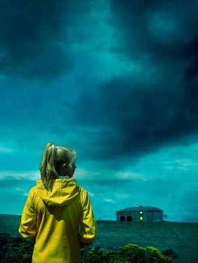 Stephen Mulcahey A female wearing a yellow raincoat, looking at a house on the horizon