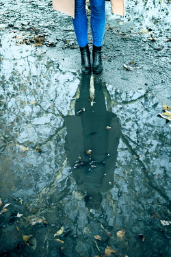 Miguel Sobreira Legs of woman in jeans standing by puddle during autumn