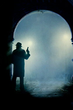Lee Avison man in overcoat and fedora holding a gun in fog at night