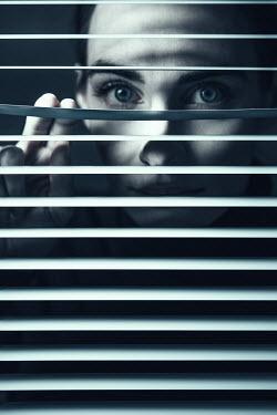 Magdalena Russocka woman peering through blinds
