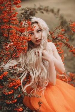 Jovana Rikalo Young woman in orange dress sitting by berry bush